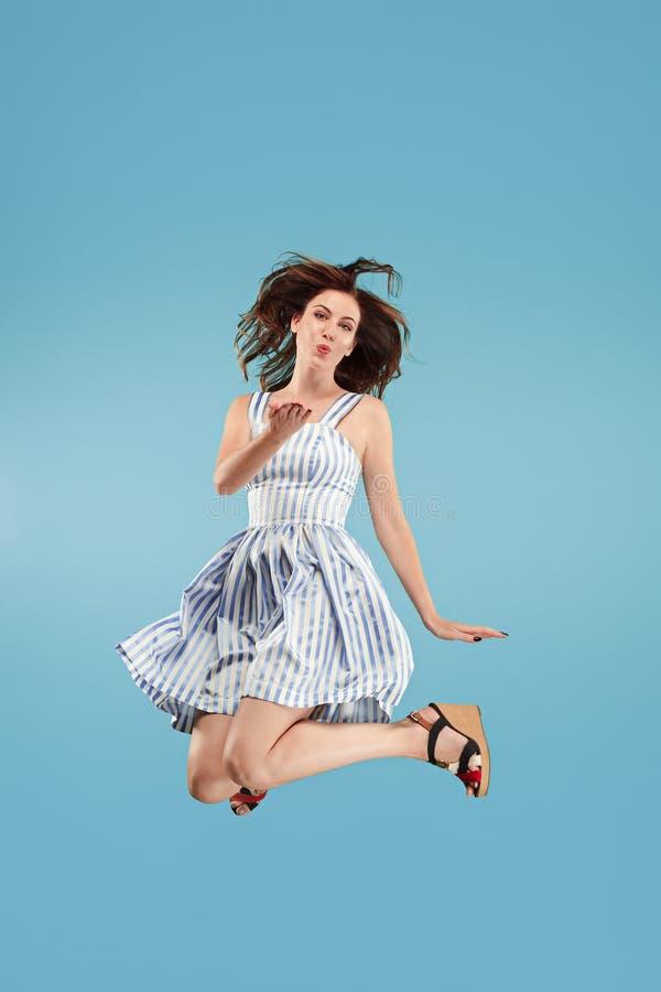 Liberté dans le déplacement Jolie jeune femme sautant sur le fond bleu image stock