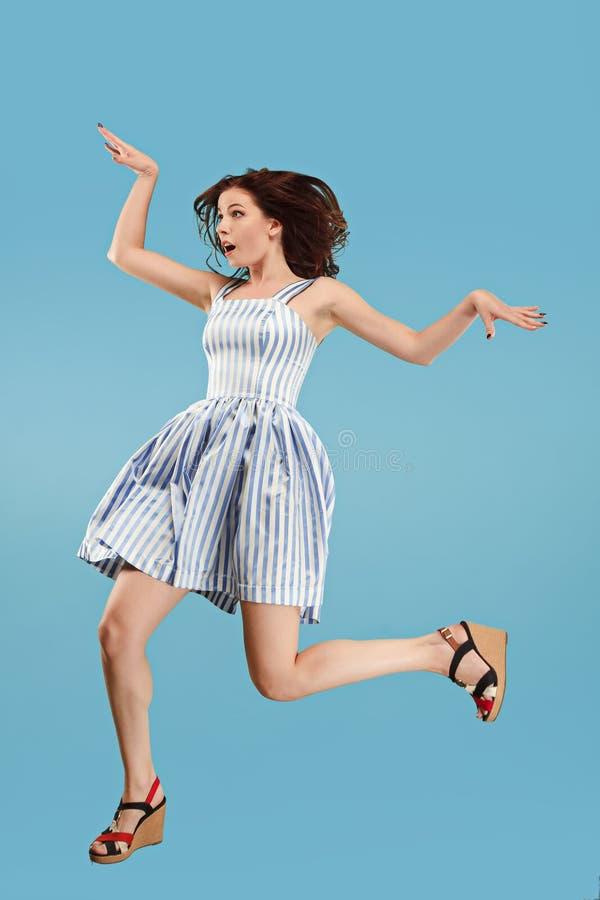 Liberté dans le déplacement Jolie jeune femme sautant sur le fond bleu photo libre de droits