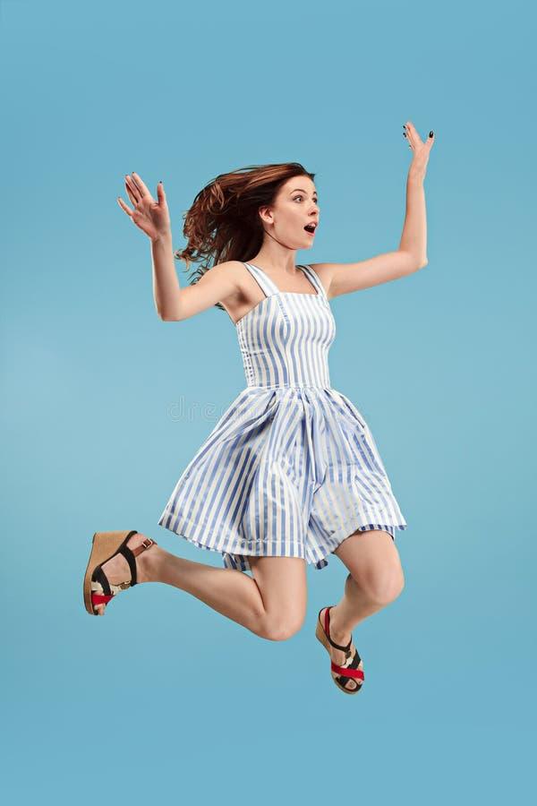 Liberté dans le déplacement Jolie jeune femme sautant sur le fond bleu photos stock