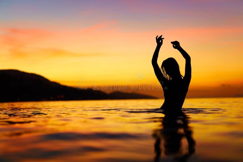 Liberté, plaisir Femme en mer au coucher du soleil Bonheur, L sain images stock