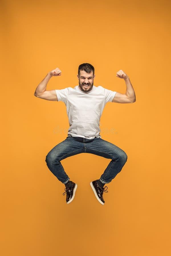 Libertad en la mudanza hombre joven hermoso que salta contra fondo anaranjado imagen de archivo