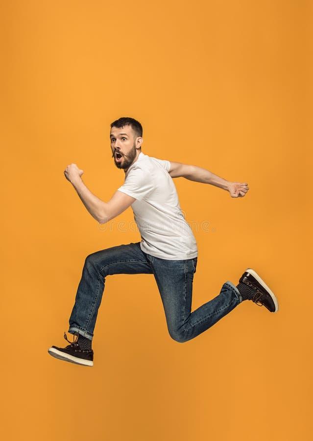Libertad en la mudanza hombre joven hermoso que salta contra fondo anaranjado imagen de archivo libre de regalías