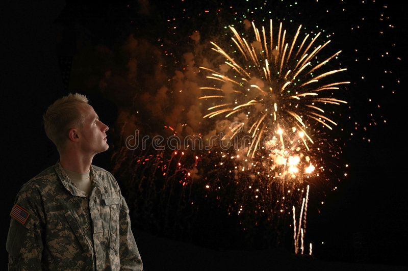 Liberty. A soldier in combat fatigues looking up at the fireworks stock images