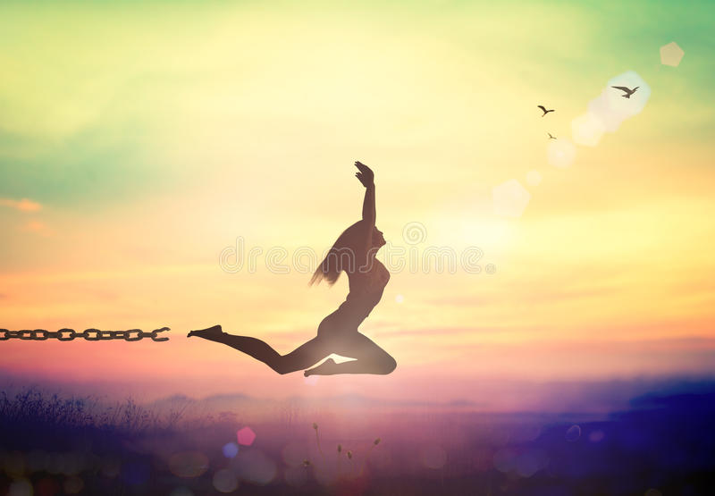 International migrants day concept. Silhouette of a girl jumping and broken chains at sunset mountain with her hands raised royalty free stock photography