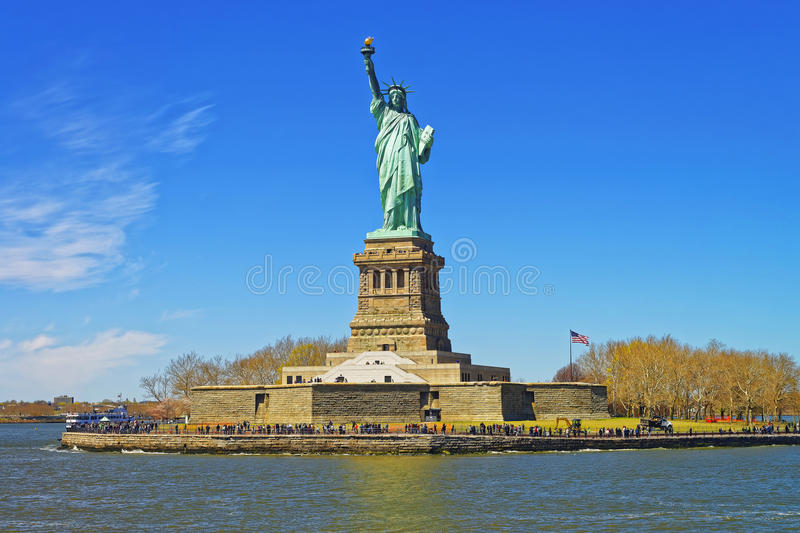 Liberty Island and Statue in Upper New York Bay. New York City, USA. In Upper New York Bay. Tourists are walking on the island royalty free stock images