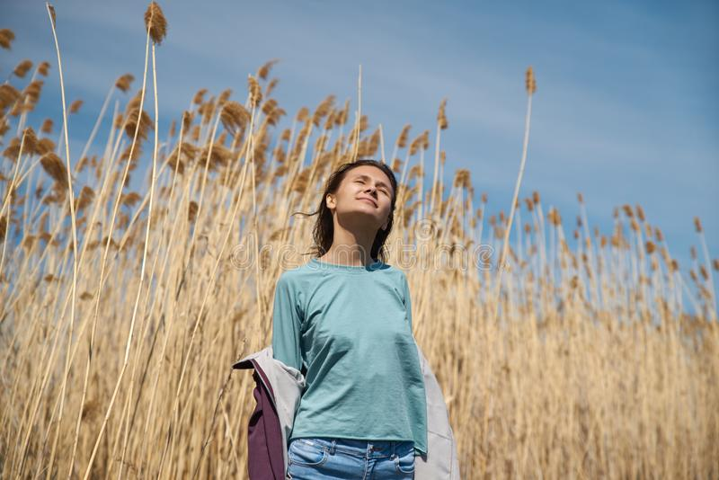 Liberty, peace of mind concept. Beautiful young woman walking in golden wheat field with cloudy blue sky background, free space royalty free stock photo