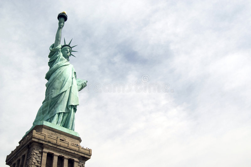 Liberty Statue. Closeup with clouds in the background in a sunny day - New York USA 2007 royalty free stock photos