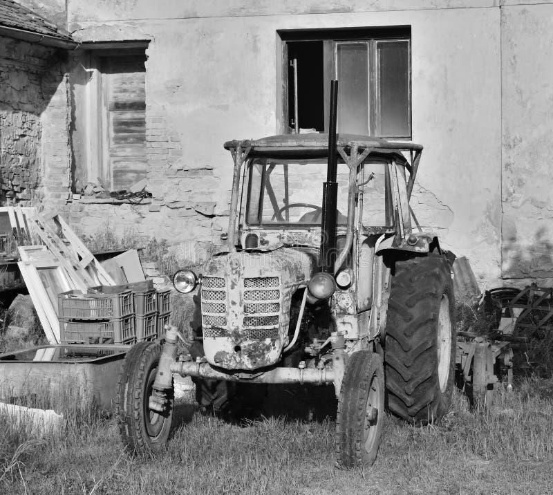 Libesice, Tsjechische republiek - 19 Mei, 2018: wrak van oude tractor voor huis in Libesice-dorp tijdens de lentezonsopgang met b stock foto