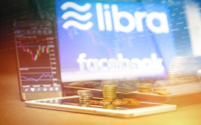 Libra coin blockchain concept / New project libra a cryptocurrency launched by Facebook stock graph charts laptop tablet royalty free illustration