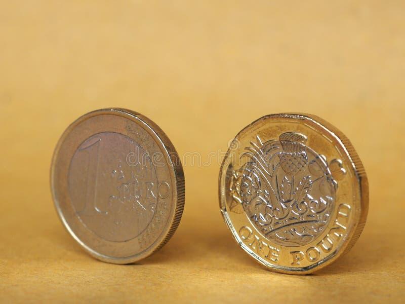 1 libra e 1 euro- moeda sobre o fundo de papel imagem de stock