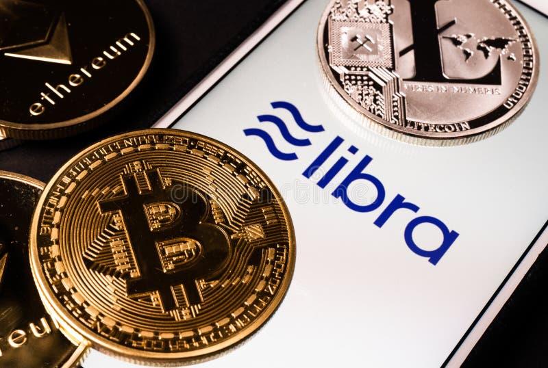 Libra o logotipo do cryptocurrency de Facebook na tela do telefone celular e em moedas reais do outro cripto tais como Bitcoin ao imagem de stock