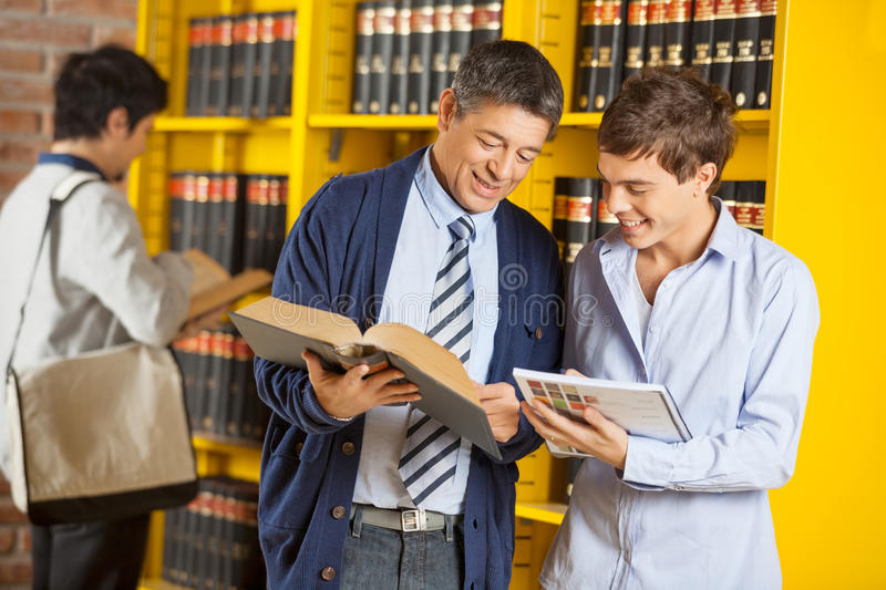 Librarian Assisting Student In University Library royalty free stock photos