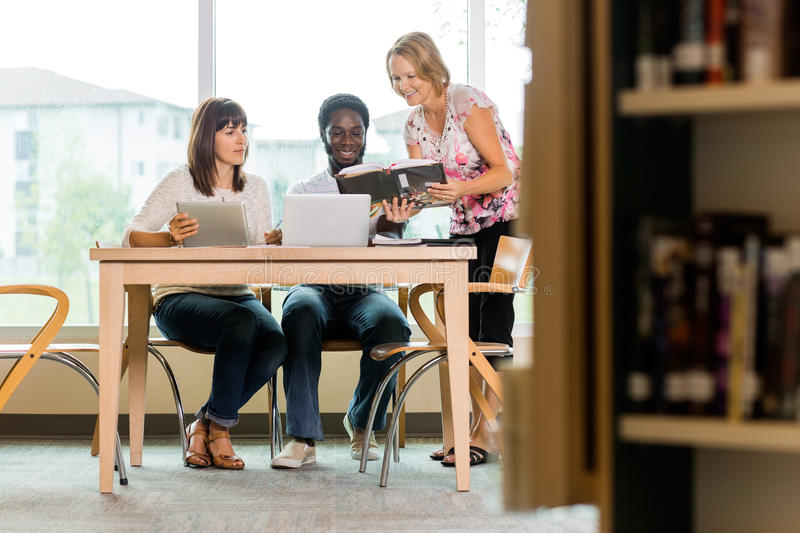 Librarian Assisting Students In Library stock images
