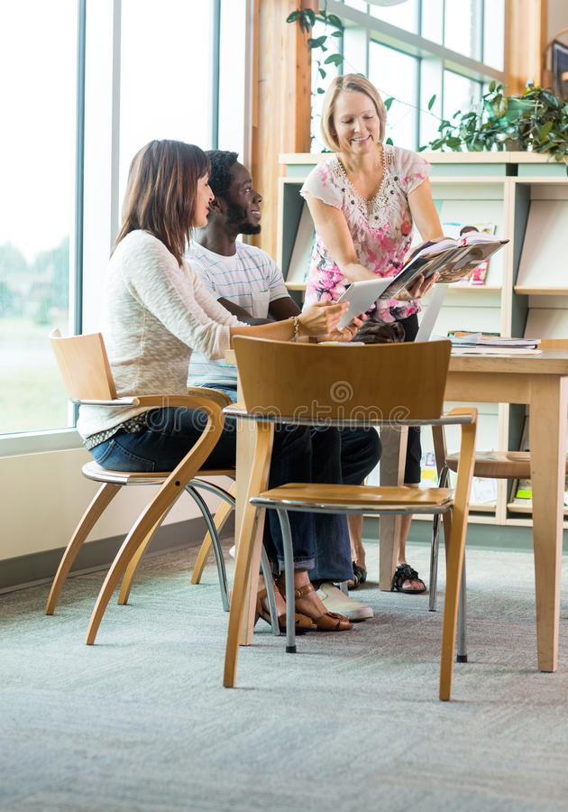 Librarian Assisting Students In Library royalty free stock photo