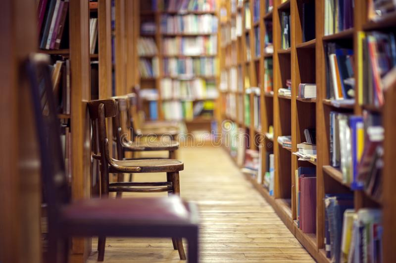 Library with books on shelf and empty chairs royalty free stock photos