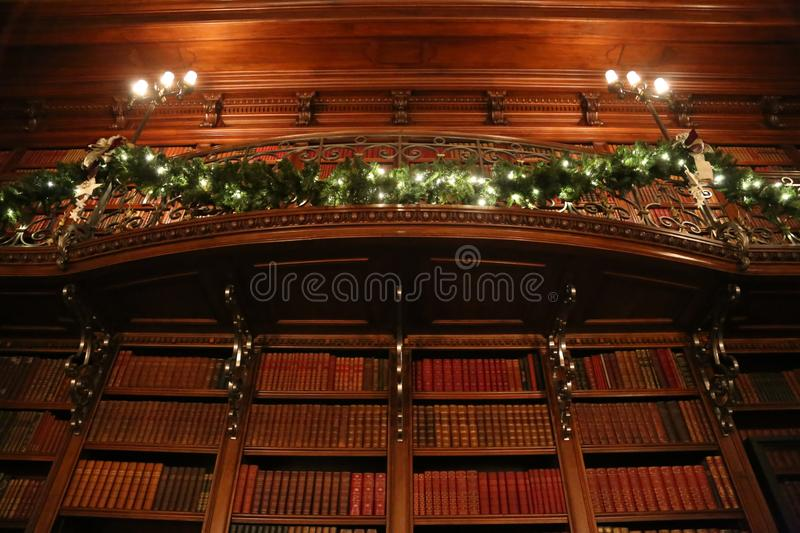 Library at Christmastime with green garland wrapped around railing and old antique books. The angle is low and captures how large the library room is stock photos