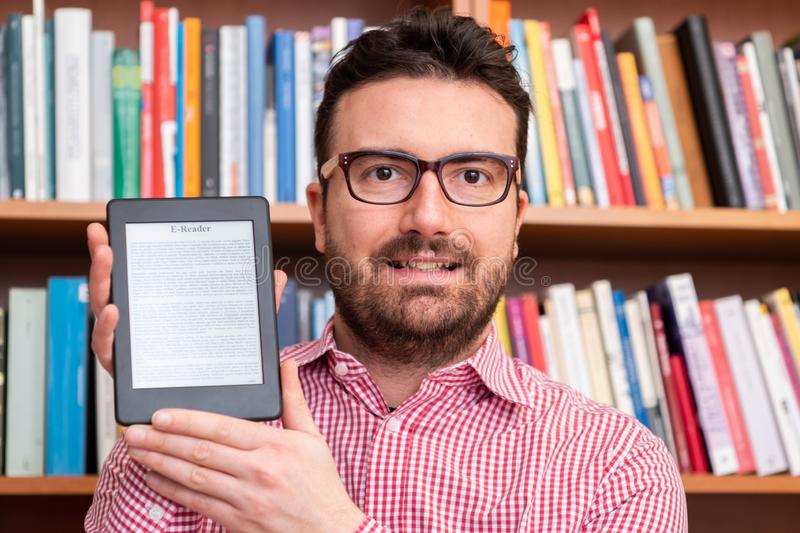 Library in only one digital ebook reader device. Holding in hands a modern ebook reader and paper books in the background royalty free stock photo