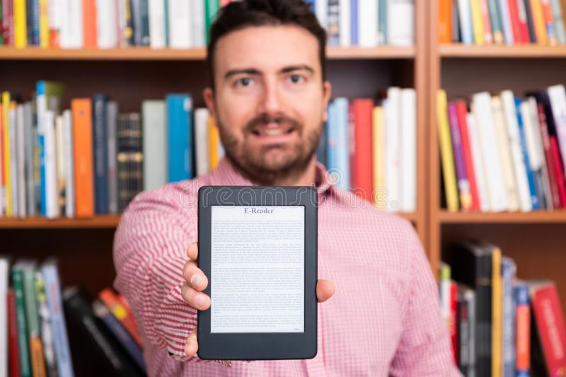 Library in only one digital ebook reader device. Holding in hands a modern ebook reader and paper books in the background stock image