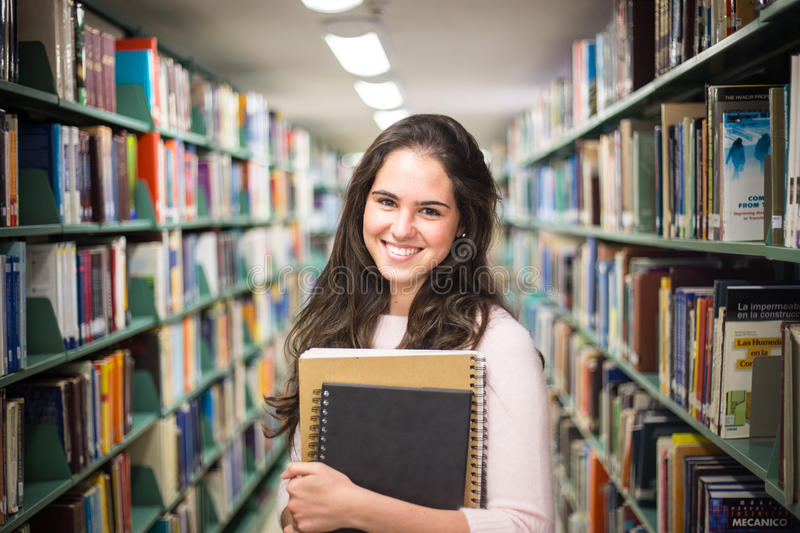 In the library - pretty female student with books working in a h royalty free stock photography