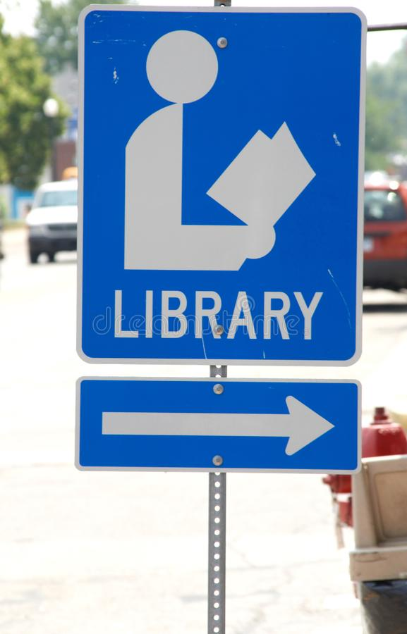 Library sign posted adjacent to a street with an arrow pointing to to its destination. Sign for the Library adjacent to a busy street royalty free stock image