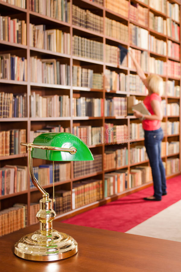 Library table lamp with female student in the background stock image download library table lamp with female student in the background stock image image of intelligence mozeypictures Choice Image