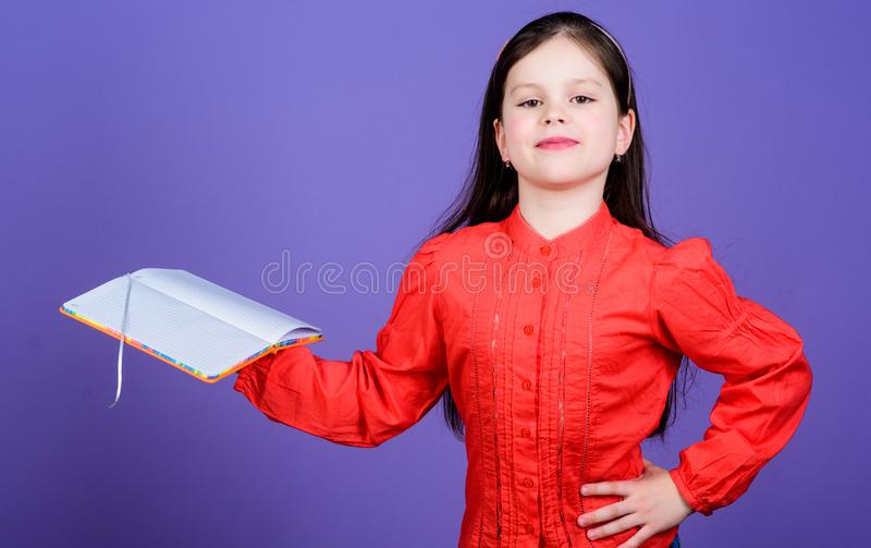 The library is the temple of learning. Confident small child holding library book. Adorable little library reader with. Open book. Reading in a school library royalty free stock photography