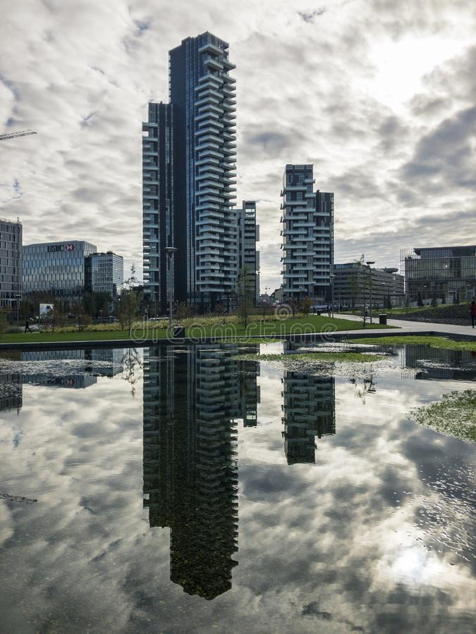 Library of trees, new Milan park. Solaria tower. Skyscrapers mirrored in the fountain. Italy. Library of trees, new Milan park. Solaria tower. 11/07/2018. Paths stock photo