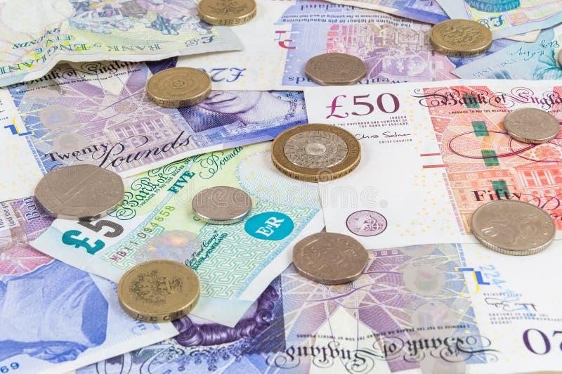 Libras britânicas das cédulas e o fundo das moedas foto de stock