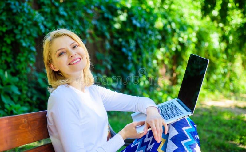 Libre accès de connexion réseau de WI fi Indépendant de Madame travaillant en parc La femme avec l'ordinateur portable travaille  image libre de droits