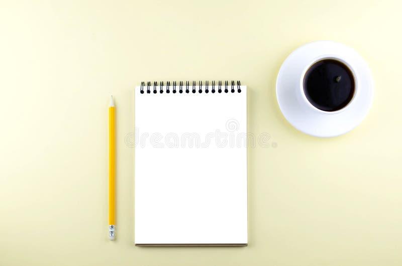 Libreta aislada con un lápiz y un café sólo en un fondo amarillo imagenes de archivo