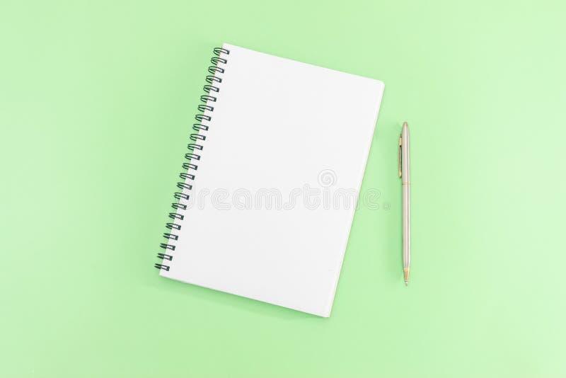 Libreta blanca con la pluma de acero en un fondo verde Tabla de la oficina, composición mínima Copie el espacio fotos de archivo libres de regalías