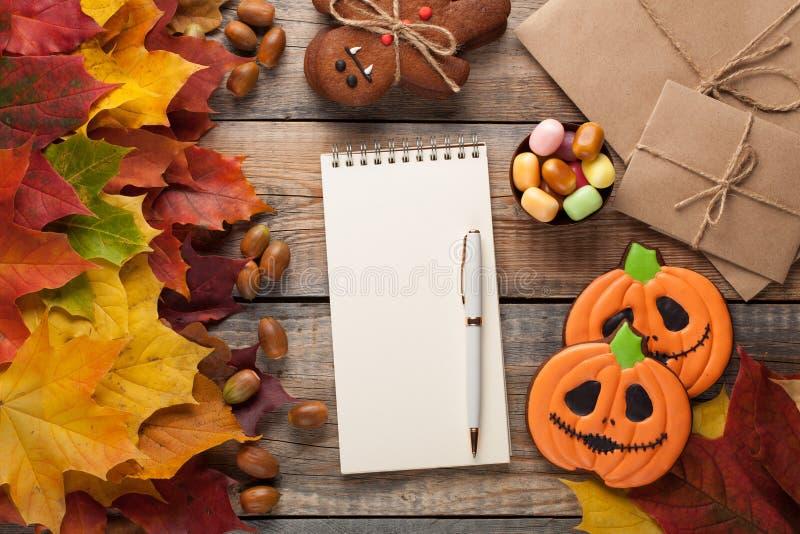Libreta blanca en blanco con la pluma en el fondo de las hojas y del caramelo de otoño en el caramelo de Halloween, las calabazas fotografía de archivo libre de regalías