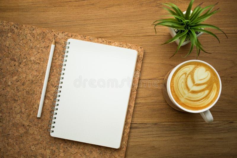 Libreta blanca en blanco con latte del café en la tabla de madera fotos de archivo