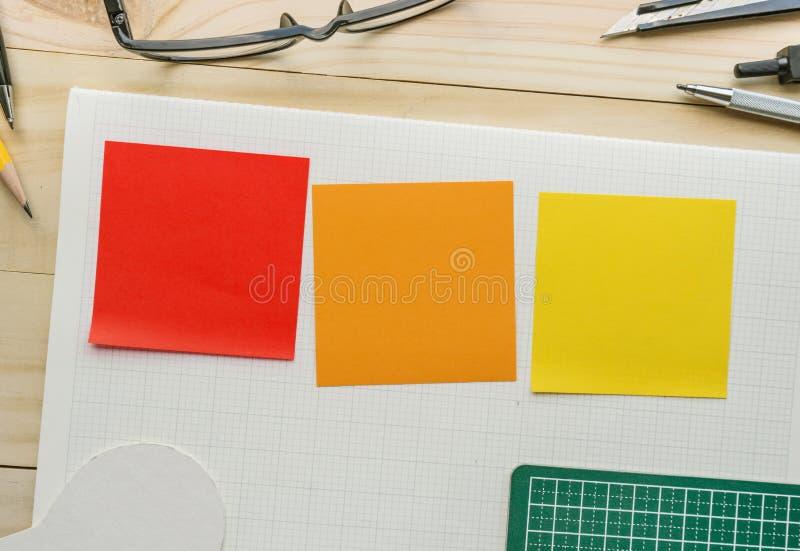 Libreta colorida en la tabla de trabajo con los elementos de herramientas, equipo foto de archivo