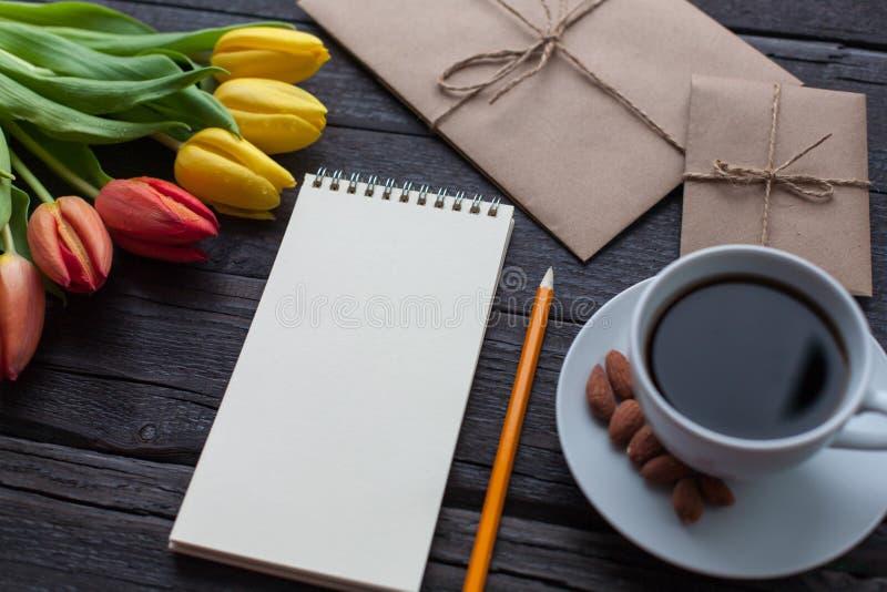 Libreta con el lápiz al lado de los tulipanes, del café, y de los sobres en fondo de madera Visión desde arriba con el espacio de foto de archivo libre de regalías