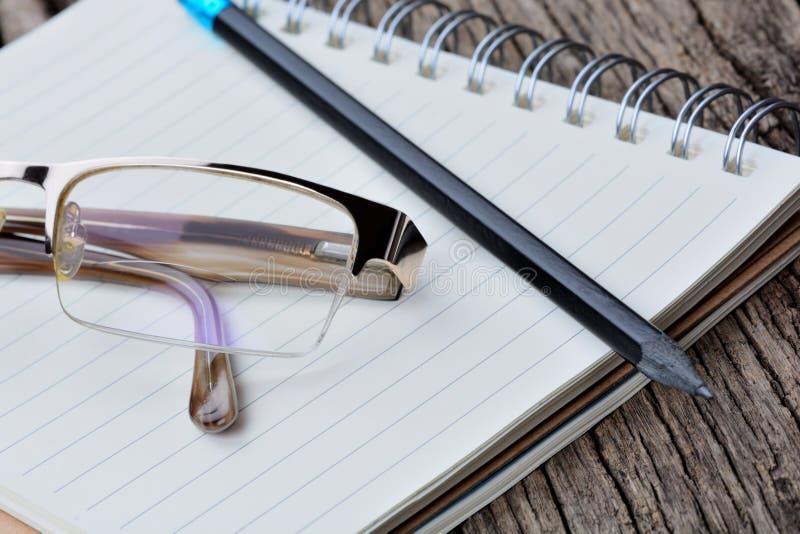 Libreta con el lápiz y las lentes en la tabla imágenes de archivo libres de regalías