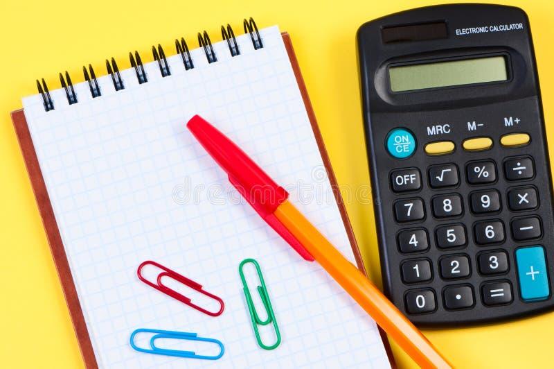Libreta con la calculadora y la pluma. fotos de archivo