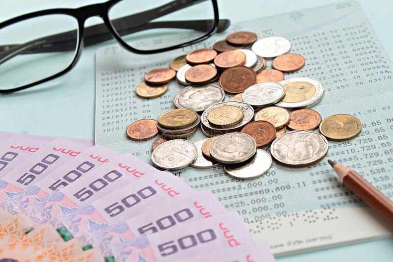 Libreta de banco del cuenta de ahorros, baht tailandés del dinero, monedas, vidrios y pluma en fondo azul foto de archivo