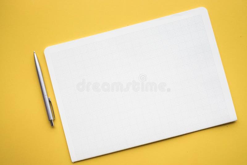 Libreta del Libro Blanco en fondos del color en colores pastel Diseño plano de la endecha fotografía de archivo