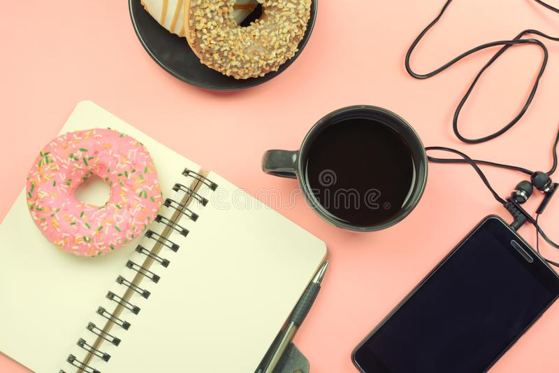 Libreta el las primaveras en un fondo rosado Al lado del cuaderno es una taza de café, de un teléfono con los auriculares y de un foto de archivo