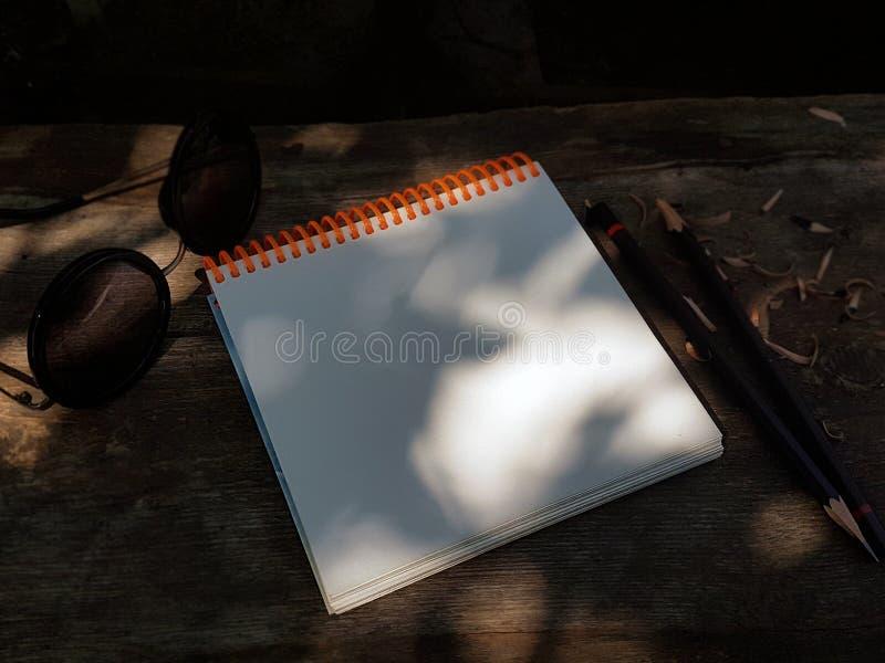Libreta en blanco abierta con white pages vacíos con un lápiz que pone en una tabla de madera fotos de archivo