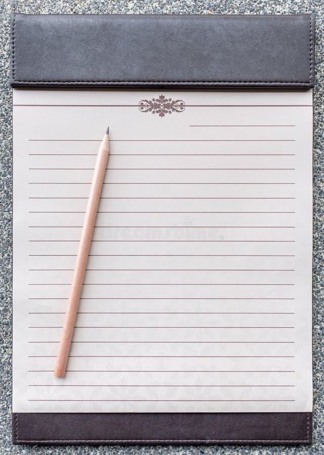 Libreta en blanco con el lápiz en el tablero marrón fotos de archivo