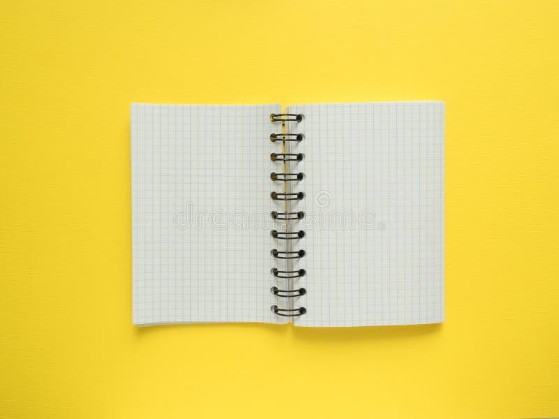 Libreta en forma ampliada en un espacio amarillo de la copia del fondo fotos de archivo