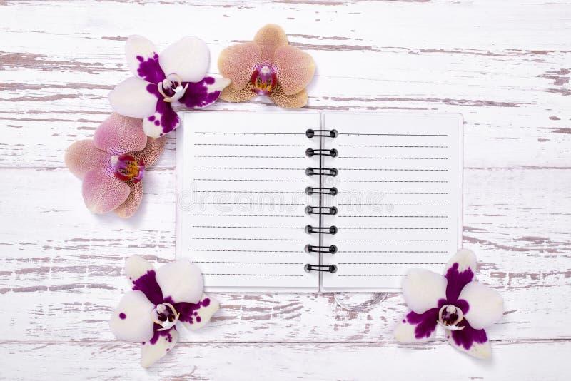 Libreta en la tabla de madera vieja adornada con las flores imágenes de archivo libres de regalías