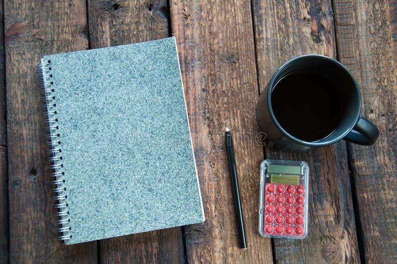Libreta gris en la tabla Al lado de una taza de café y de una pluma En de madera fotos de archivo