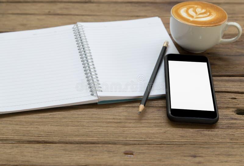 Libreta, lápiz, café y teléfono móvil en la tabla de madera fotografía de archivo libre de regalías