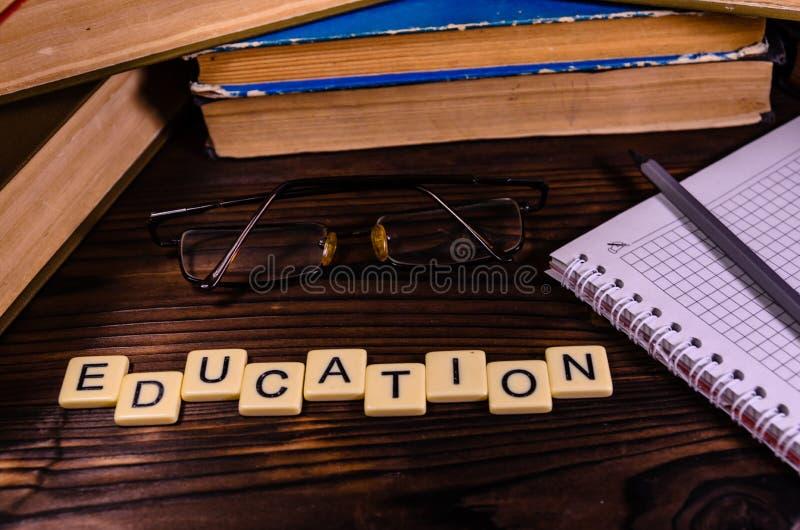 Libreta, lápiz y lentes delante de los libros Insc de la educación imagen de archivo