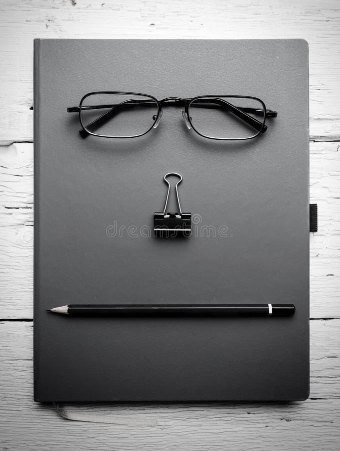 Libreta, lentes, paperclip y lápiz en la tabla de madera fotos de archivo libres de regalías