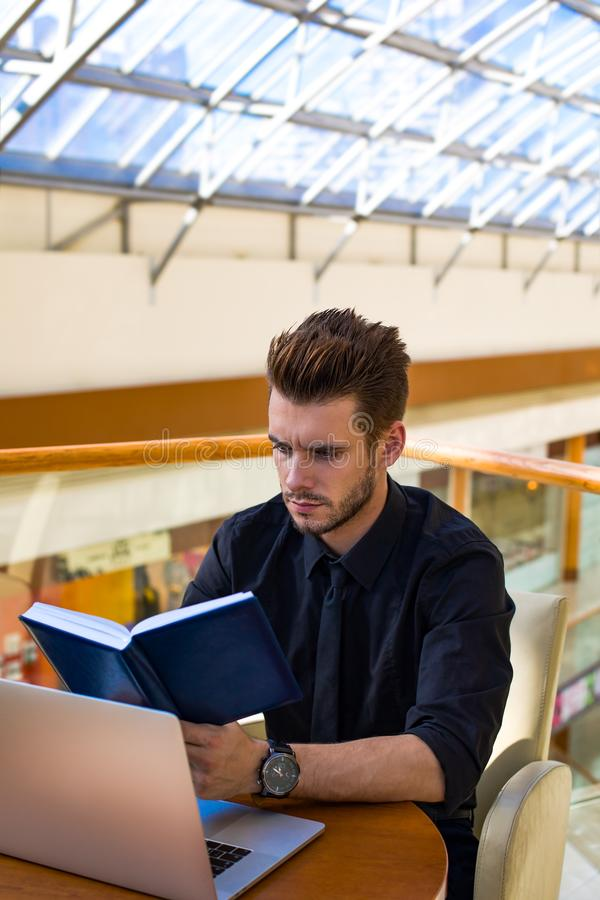 Libreta masculina barbuda de la tenencia del encargado durante webinar en el netbook, sentándose en interior de la oficina imágenes de archivo libres de regalías