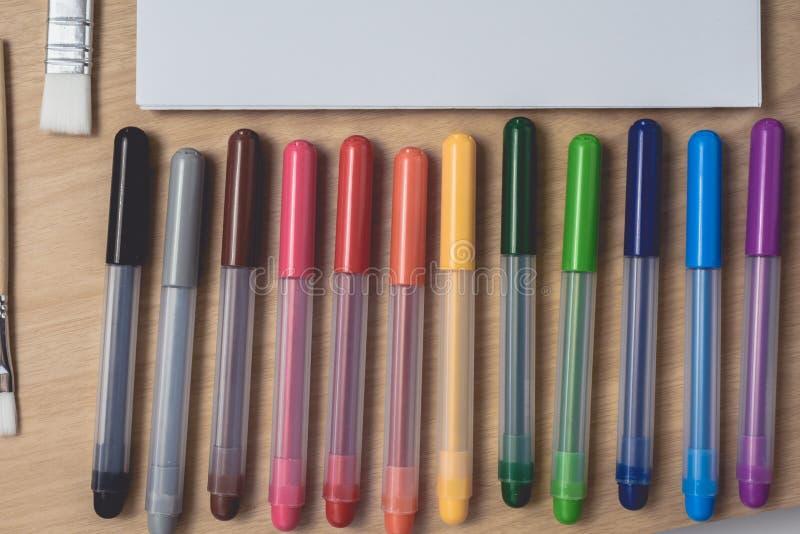 Libreta o cuaderno con muchas plumas coloridas, la brocha y la paleta de la acuarela en la tabla de madera marrón el usar para lo imágenes de archivo libres de regalías